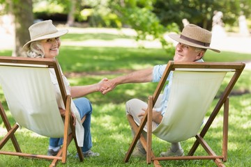 Relaxed mature couple sitting in deck chairs at park