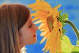 Garden, beautiful girl is smelling sunflower