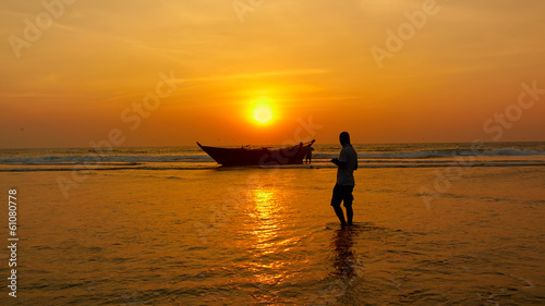 Fisherman and boat against the setting sun