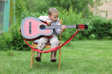 little boy play in guitar outdoors