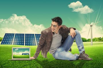 Giovane uomo con laptop seduto in un parco energetico