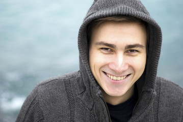 Young man smiling outdoors, portrait