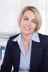 Reife Frau im Portrait sitzend im Büro
