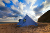 Conical tent on summer beach and blue sky with clouds