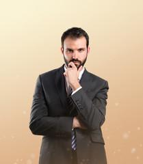 business man thinking over ocher background
