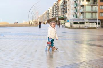 Cute toddler girl walks on the promenade along winter beach