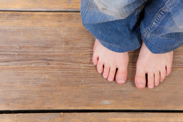 Barefoot girl standing on wooden floor