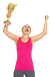 Happy fitness young woman with gold trophy cup rejoicing