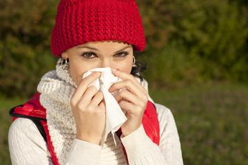 Junge Frau mit Taschentuch und Schnupfen