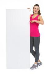 Full length portrait of fitness woman showing blank billboard