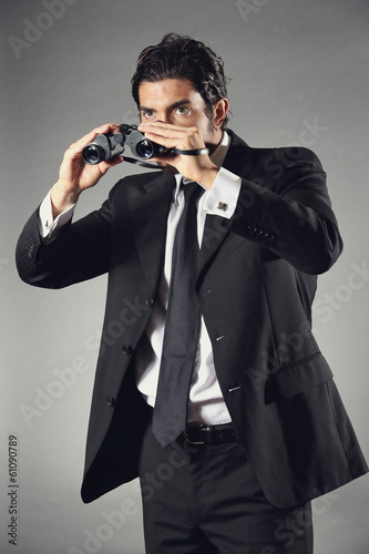Elegant businessman with binocular