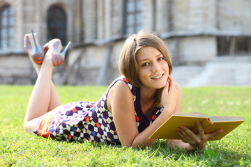 Happy woman reading book on green grass