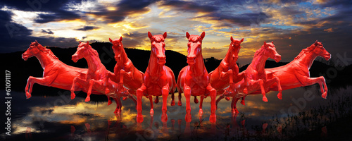 Group of red horses running with sunset sky background