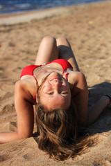 Brunette woman sunbathing on a beach