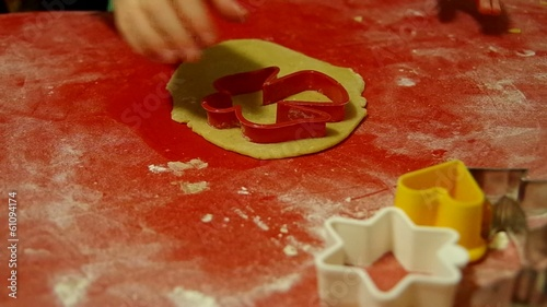 Girl preparing gingerbread from dough.