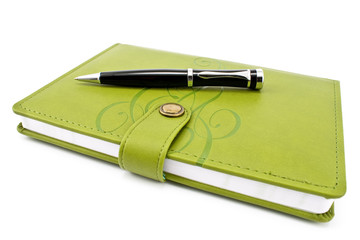 Pen and green notebook isolated on white