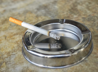 Metal ashtray with a cigarette on a marble table