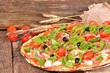 Italian pizza with ham, mozzarella and arugula