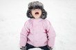 Little girl sitting in snow, she is cold, angry and crying. - 61096933