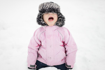 Little girl sitting in snow, she is cold, angry and crying.