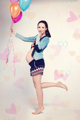 Pregnant woman with colorful balloons