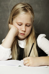 Girl writing in classroom - test or examination