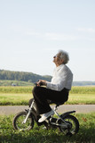Happy senior woman riding bicycle for toddlers.