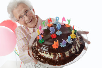 Happy senior woman holding her birthday cake.