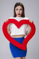 Young attractive woman holding a red valentines heart