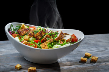 Caesar salad with hot chicken and fresh vegetables