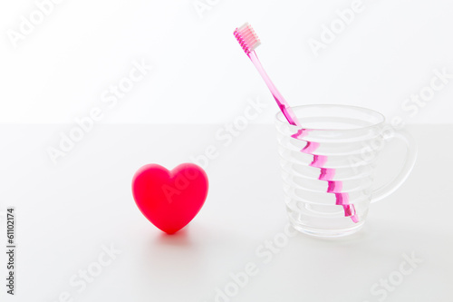 toothbrush and heart on white background