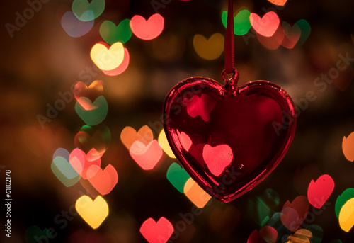 Red glass heart against colourful heart-shaped bokeh