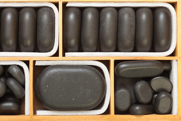 Black spa zen massage stones in wooden case as background