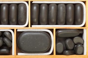 Black spa zen massage stones in wooden case as background