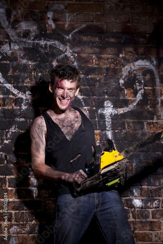 Horrific madman on a dark background and chainesaw