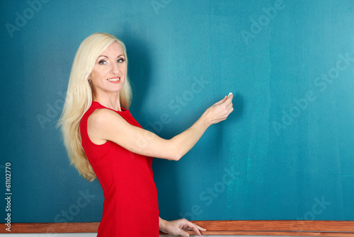 School teacher writes in chalk on blackboard