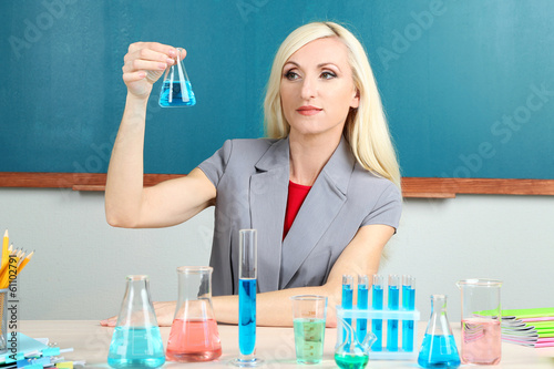 Chemistry teacher with tubes sitting at table