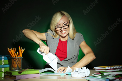 Wicked teacher sitting at table on dark colorful background