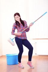 Young housewife with  mop in room