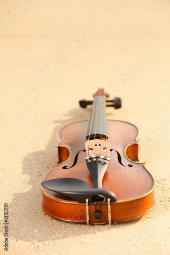 Violin on sandy beach. Music concept