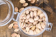Pistachio nuts in glass jar on wooden background