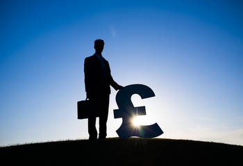Silhouette of Businessman Holding Pound Currency
