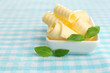 Curls of fresh butter with basil in bowl, on blue tablecloth