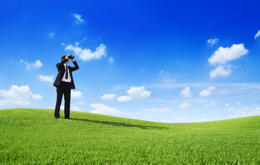 Businessman with Binoculars on a Hill