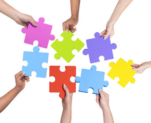 Human Hands Holding Jigsaw Puzzle