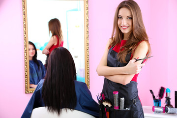 Beautiful girl hairdresser and client in beauty salon