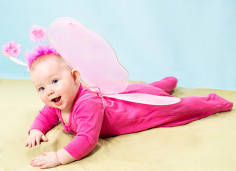 Pretty child girl, dressed in butterfly costume on  background