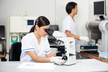 Female Scientist Using Microscope In Lab