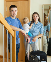 middle-aged couple with toddler with suitcases