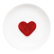 Red heart on a plate close-up isolated on a white background